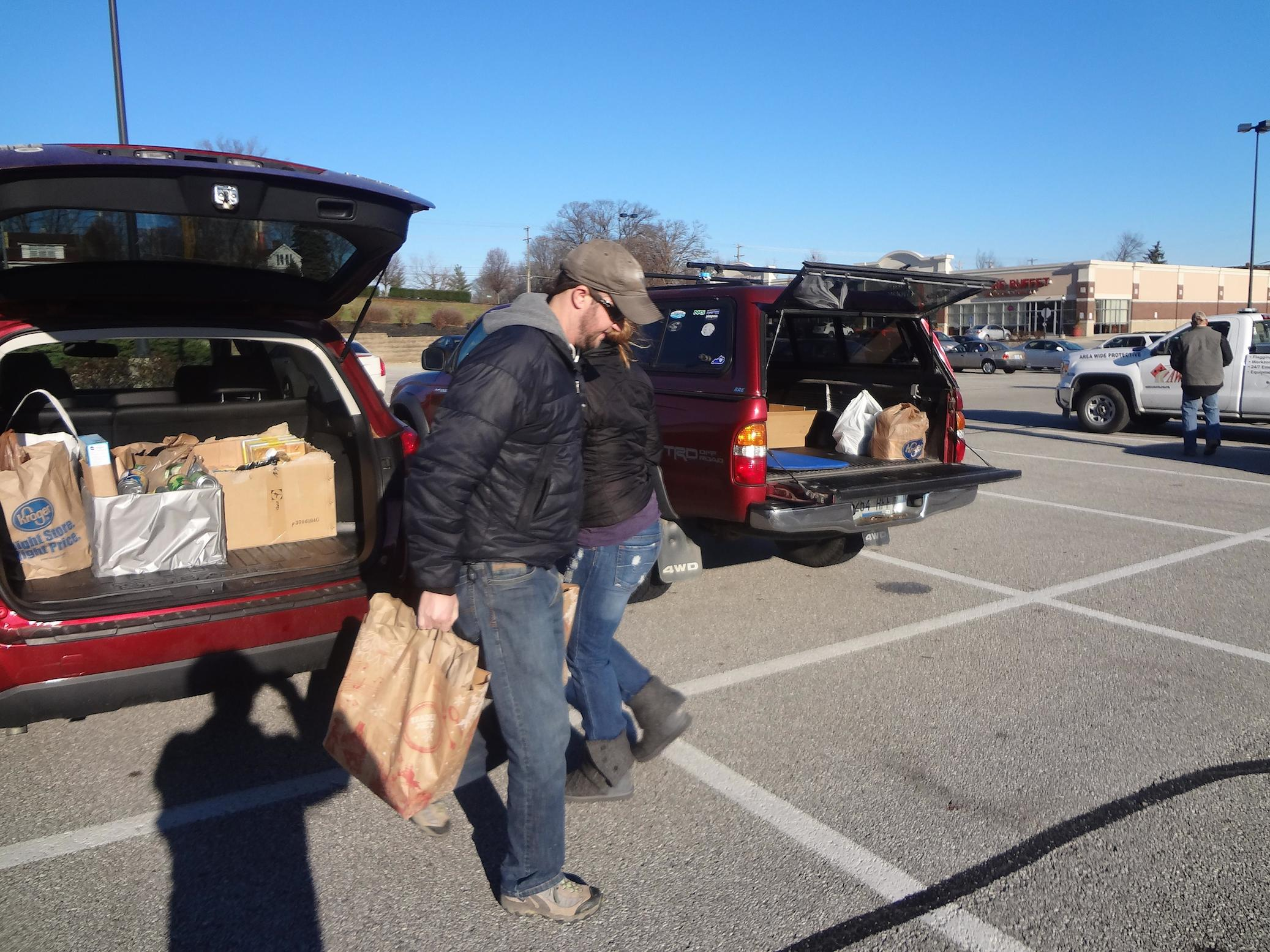 photo of volunteers unloading donated goods from a car